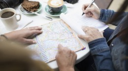 Women friends planning with map, drinking coffee at sidewalk cafe