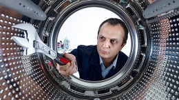 Repairman servicing washing machine.