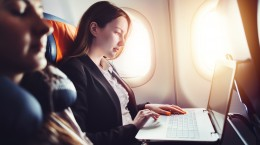 Female entrepreneur working on laptop sitting near window in an airplane.